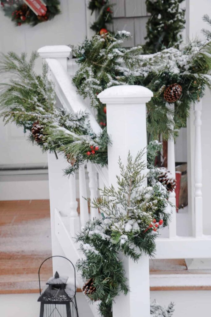 garland on snow covered porch