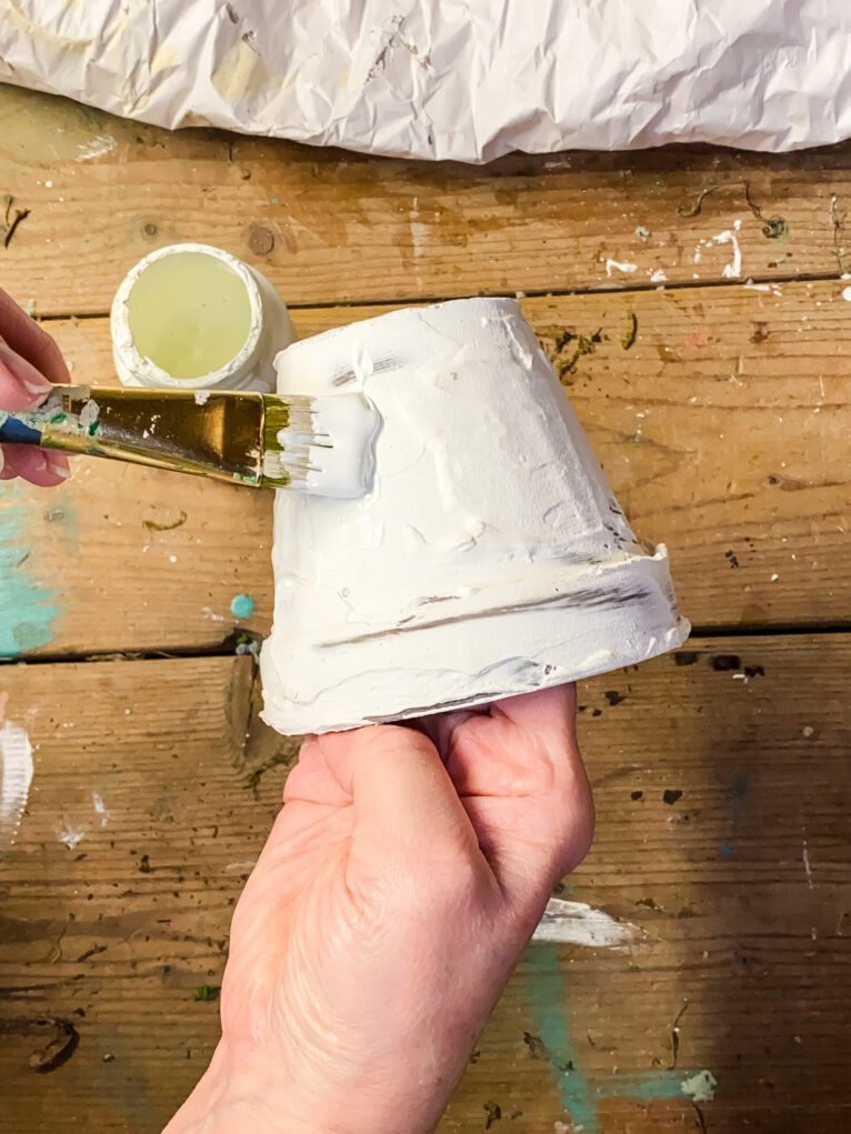 painting a clay pot